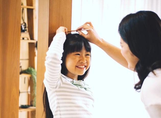 身長を測る少女と母親