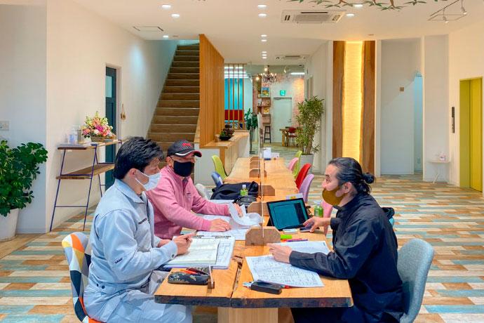 大久保店の天然木一枚板のテーブルで打ち合わせをする一級建築士長谷川渉先生