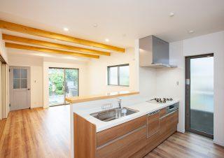 リビングダイニングを見渡せるカウンターキッチン。カウンターは天然木の一枚板を使用。リビングの天井には化粧梁を施しおしゃれな空間に。