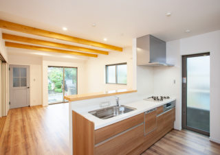 リビングダイニングを見渡せるカウンターキッチン。カウンターは天然木の一枚板を使用。リビングの天井には化粧梁を施しおしゃれな空間に|京都・滋賀の注文住宅 天然木の家