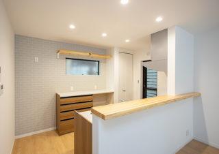 天然木一枚板のキッチンカウンターにカップボードの上部にも天然木一枚板を利用した棚を設置|京都・滋賀の注文住宅 天然木の家